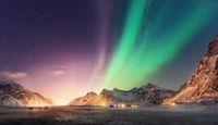 Green and purple aurora borealis over snowy mountains