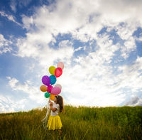 Smiling kid having fun with balloons outdoors