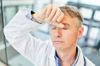 Arzt mit der Hand an der Stirn für Erschöpfung