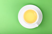 White cup of oolong tea over green
