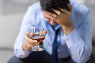 drunk man with glass of alcohol at home