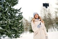 woman taking picture by selfie stick in winter