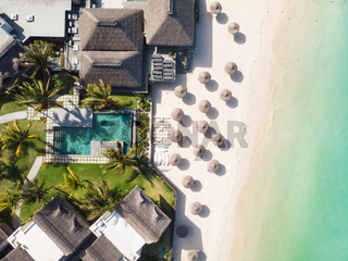 Aerial view of amazing tropical white sandy beach with palm leaves umbrellas and turquoise sea, Mauritius.