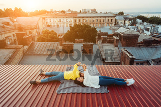 A handsome guy and a young girl lie on the roof and hold the smarfons.