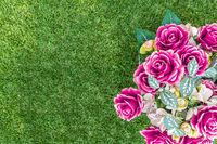 Plastic flowers on green grass