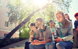 group of teenage friends with smartphones outdoors