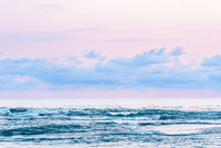 View of the blue sea with pink sunset light