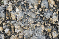 Pebble stones in a rocky wall. Natural background of a rocky stone wall