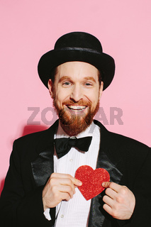 Happy man in a tuxedo and top hat holding a red heart