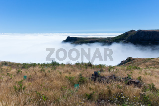 Aerial view form top of Madeira mountains with a cloud cover over the Ocean