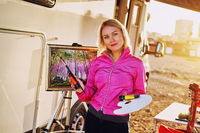 Attractive painter middle aged blond woman holds paint brush
