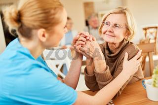 Senior Frau wird von Altenpflegerin getröstet