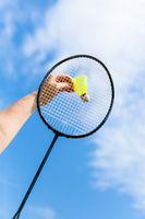 hand strikes shuttlecock by badminton racquet