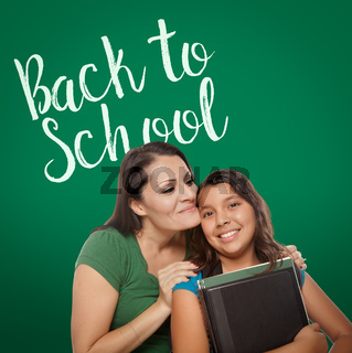 Back To School Written On Chalk Board Behind Proud Hispanic Mother and Daughter Student