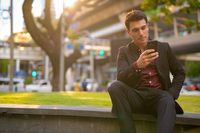 Young handsome Hispanic businessman using phone and sitting with nature in city