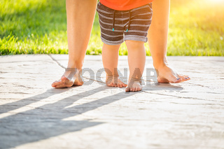 Mother and Baby Feet Taking Steps Outdoors
