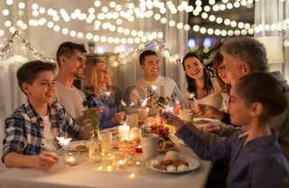 family with sparklers having dinner party at home