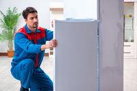 Professional contractor repairing broken fridge