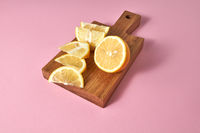Juicy yellow slices of ripe lemon - ingredients for preparind natural detox beverage for diet. Citrus fruit on a wooden board on a pink.