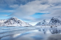 Snowy mountains and blue sky with clouds reflected in water