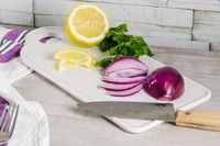 Sliced red onion, lemon and parsley leaves