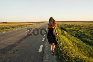 A young girl is walking along the road.