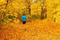 man running autumn forest park