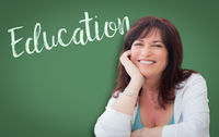 Education Written On Green Chalkboard Behind Smiling Middle Aged Woman