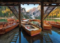 Wooden boats near the house in Braies lake at sunrise in autumn