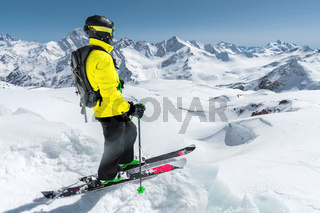 Portrait of a professional freerider skier standing on a snowy slope against the background of snow-capped mountains. The concept of winter sports