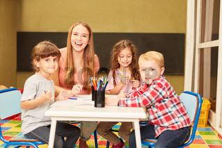 Lachende Kindergärtnerin und Kinder Gruppe