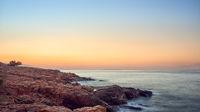 Colorful orange sunset over a rocky coastline