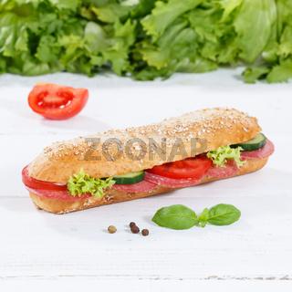Sandwich Baguette Vollkorn Brötchen belegt mit Salami Schinken Quadrat auf Holzbrett