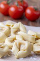 Rohe Tortellini auf Holz mit Tomaten