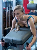 In gym. Sexy girl during training on simulator