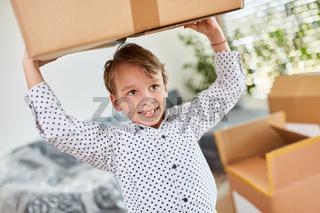 Glücklicher Junge trägt einen Umzugskarton