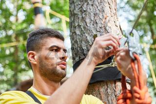 Junger Mann im Kletterwald prüft Karabiner Sicherung