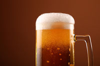 Close up pouring frothy beer in glass over brown