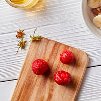 Ripe strawberry and strawberry stalks on a wooden board on a white wooden table.Top view