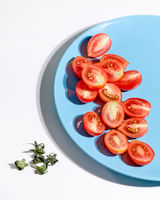 Halved ripe tomatoes in a blue plate on a gray background with shadows and copy space. Ingredients for salad. Top view