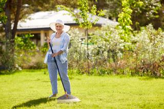 senior woman with lawn rake working at garden