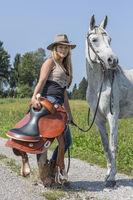 Mädchen mit Reitsattel und Pferd