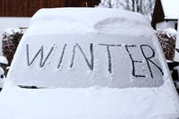 winter Schriftzug auf verschneiter Autoscheibe