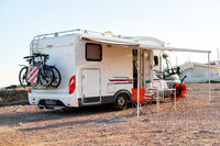 Empty folding chairs and table under canopy near recreational vehicle camper trailer. Adventure journey