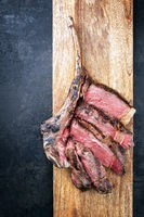 Barbecue dry aged wagyu tomahawk steak sliced as top view on a wooden board with copy space