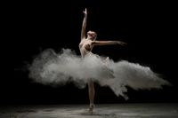 Girl topless in pointe in a burst of white powder