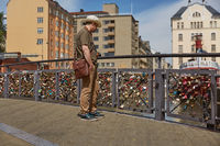 Tourist man observing lovelocks attached to a bridge of love railing in central Helsinki, Finland