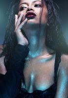 Portrait of sensual woman wearing black bra in blue neon light studio