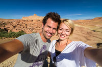 Active happy couple taking selfie on travel at Ait Benhaddou kasbah, Ouarzazate, Morocco.