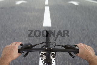 View at road from bicycle. POV to way and bike handlebar